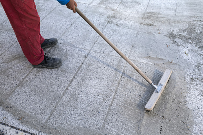 Install polymeric sand by brooming it into the paver joints during construction works. Some motion blur present.